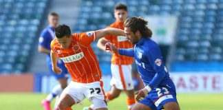 Blackpool's Jose Miguel Cubero (left) is challenged by Gillingham's Bradley Dack